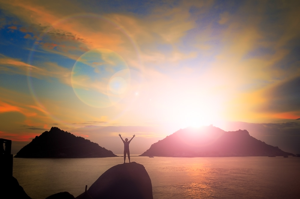 Man With Arms Up And Sunset Behind Island