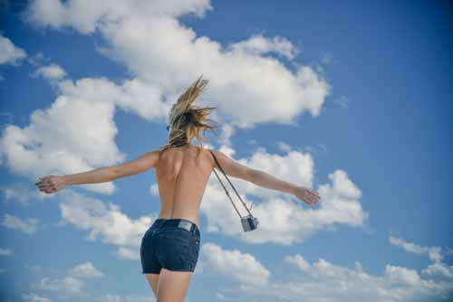 Girl Playfully Spinning In The Sun With Camera And No bikini