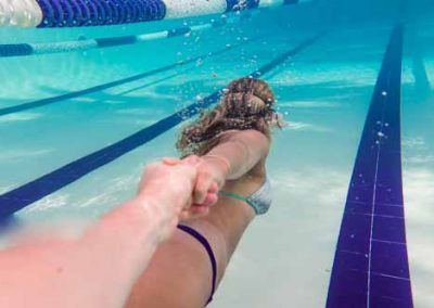 Girl Holding Mans Hand Whilst Swimming Underwater