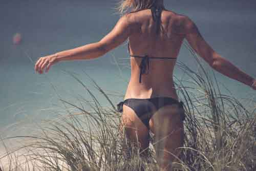 Back Of Attractive Girl Wearing Bikini Walking Through Grass On A Beach