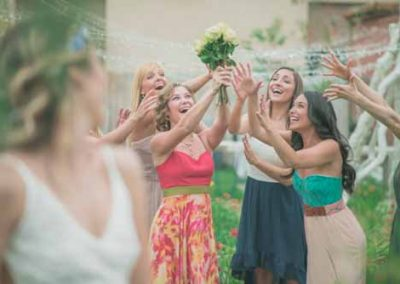 Happy Girls Catching Brides Bouquet At Outdoor Wedding